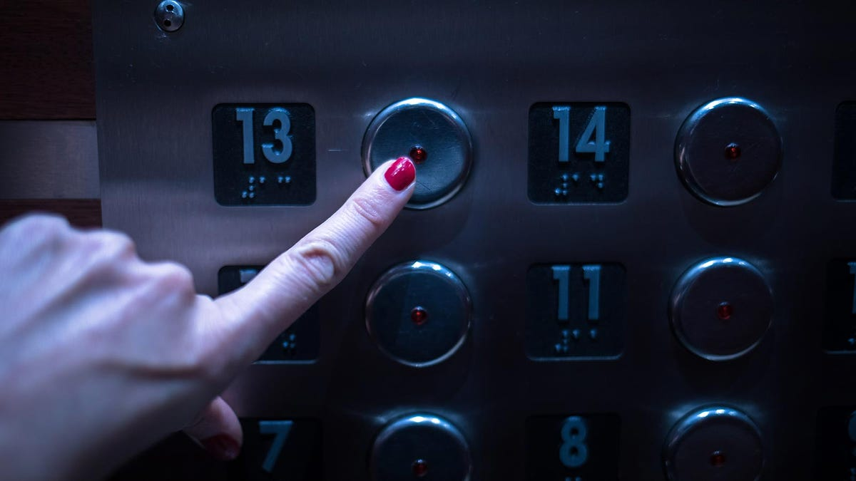 A woman's finger pressing the button for the 13th floor in an elevator.
