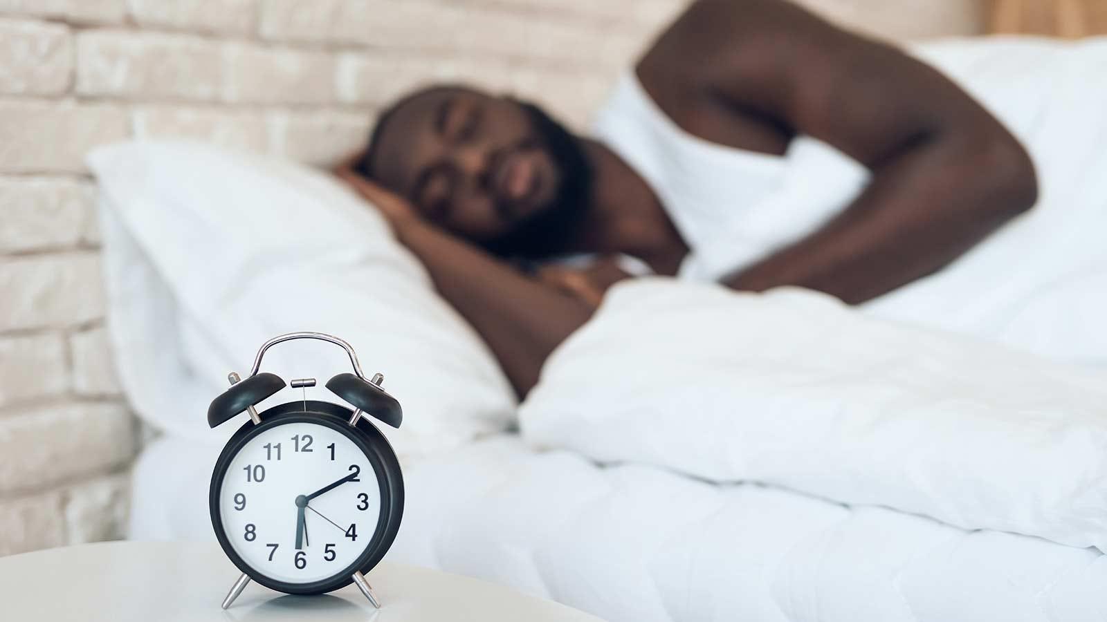 Man sleeping with an alarm clock.