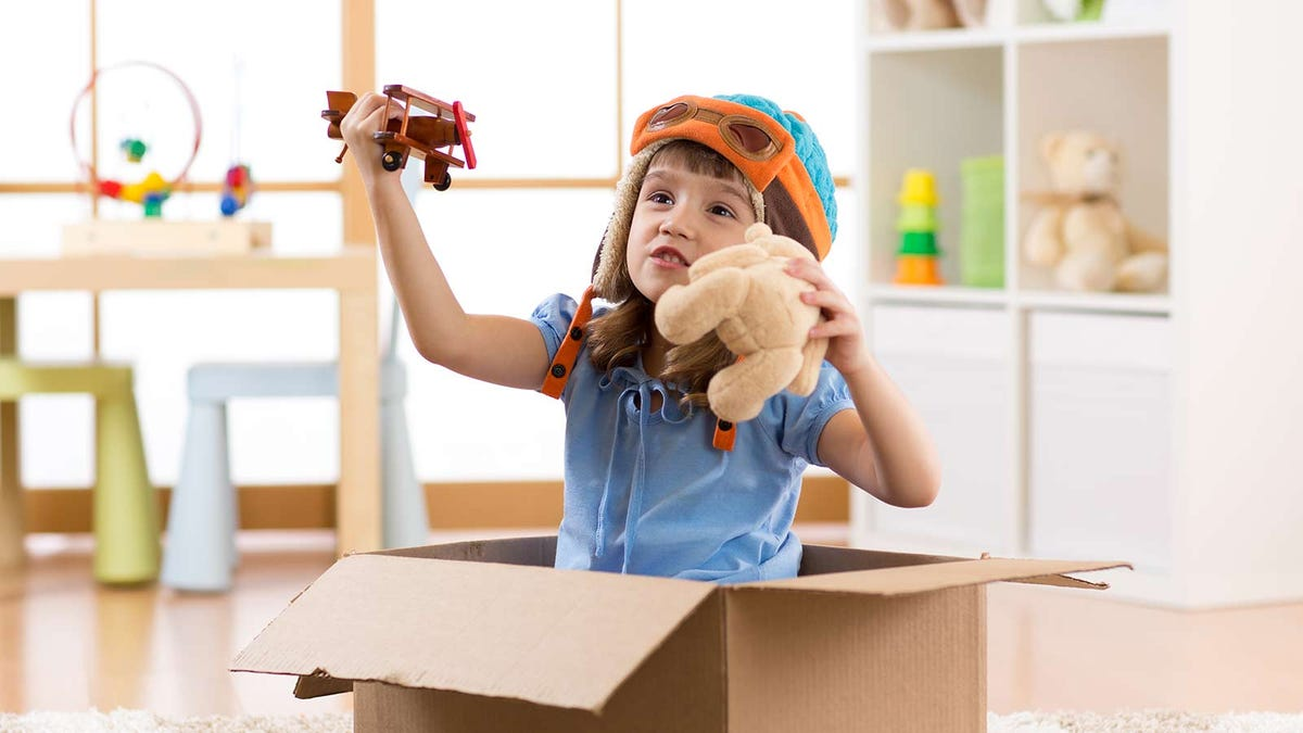 A little girl in a cardboard box playing with a plane and stuffed bear.