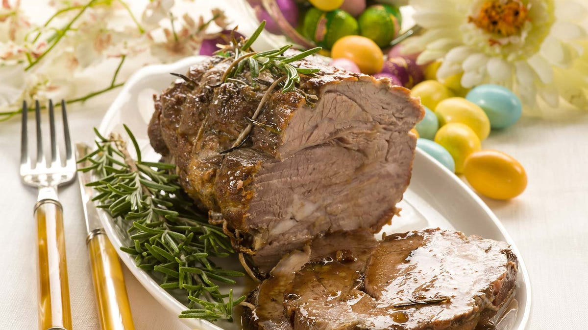 Roasted lamb on a platter covered in sprigs of rosemary.