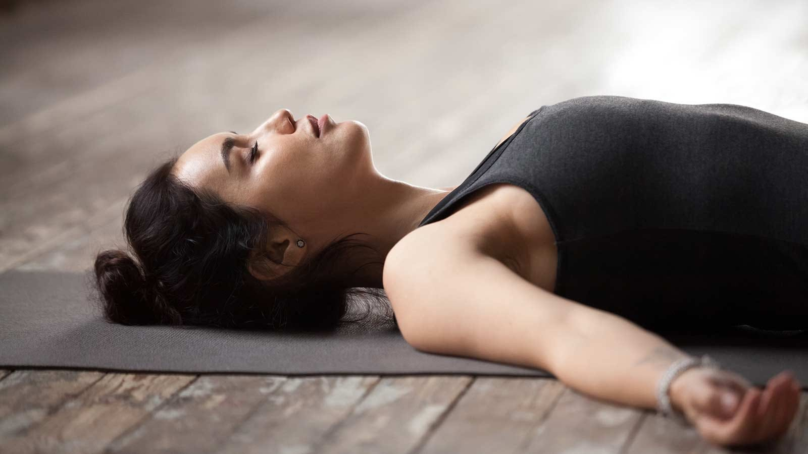 Woman lying on a yoga mat doing a breathing exercise.