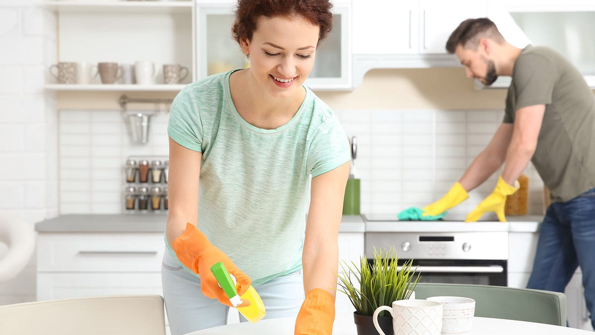 A woman and man wearing rubber gloves and cleaning a kitchen.