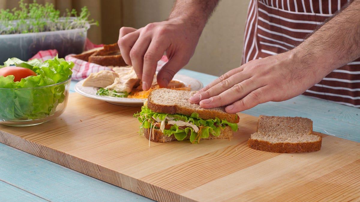 A man's hands preparing a sandwich on a counter.