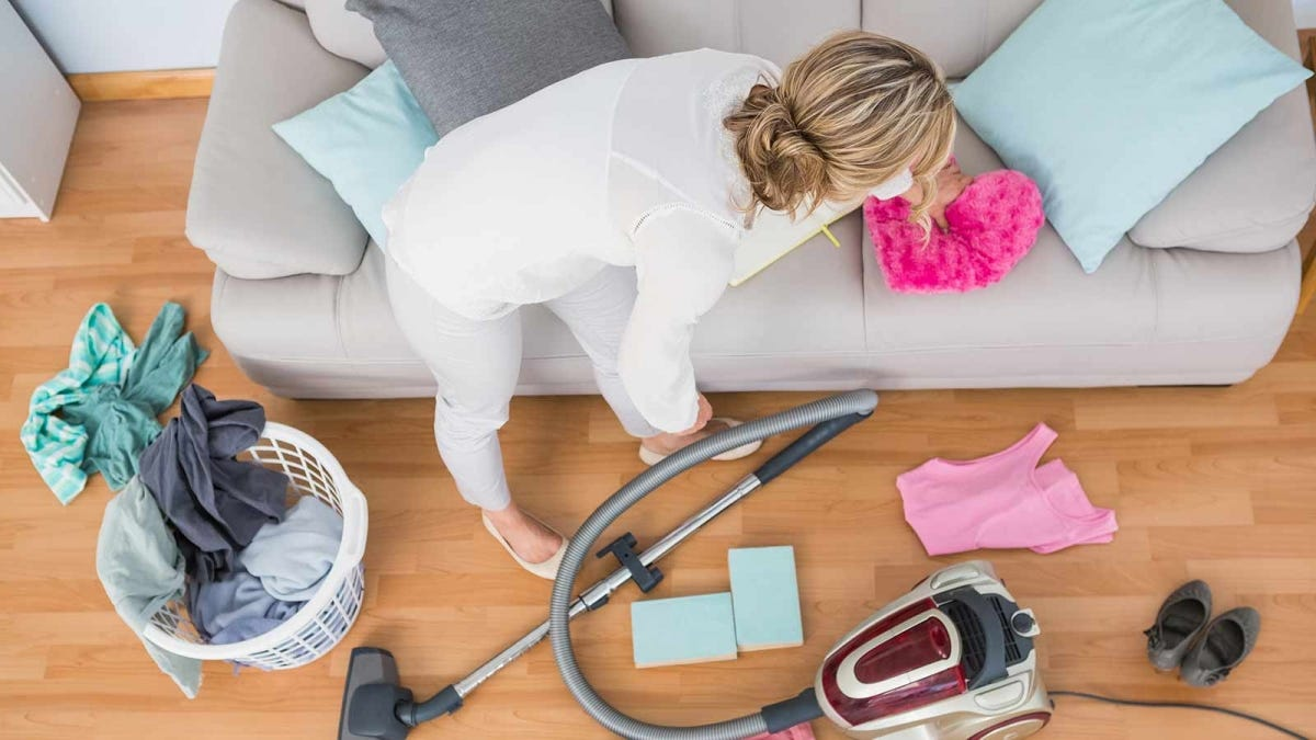 woman vacuuming her couch and floor