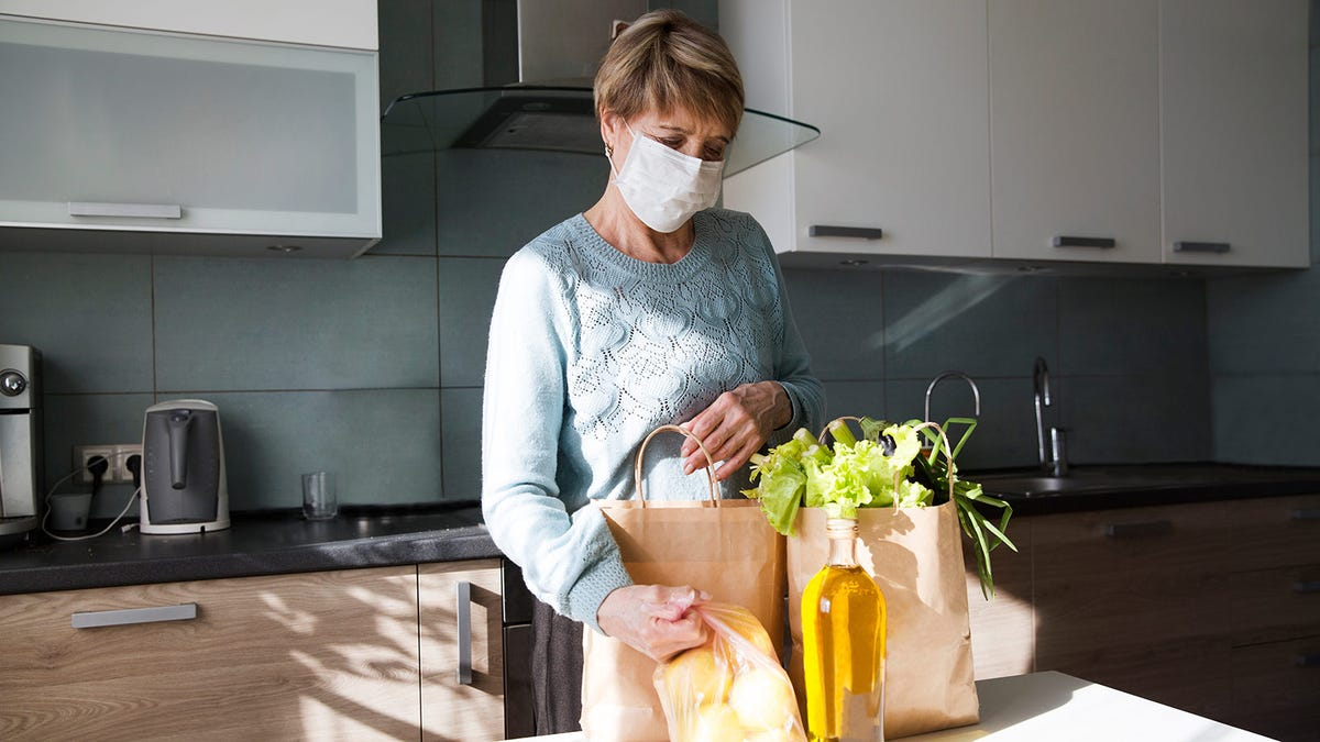 Older woman with surgical mask on, unpacking her groceries.