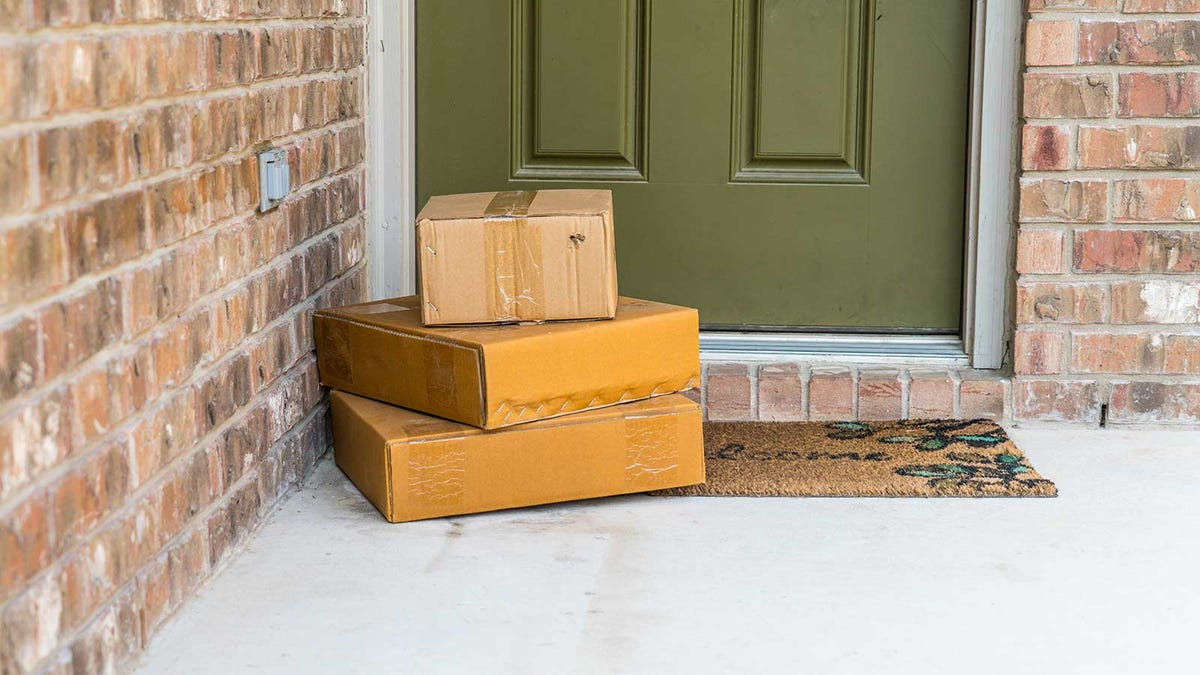A pile of packages sitting on a porch outside someone's front door on their welcome mat.