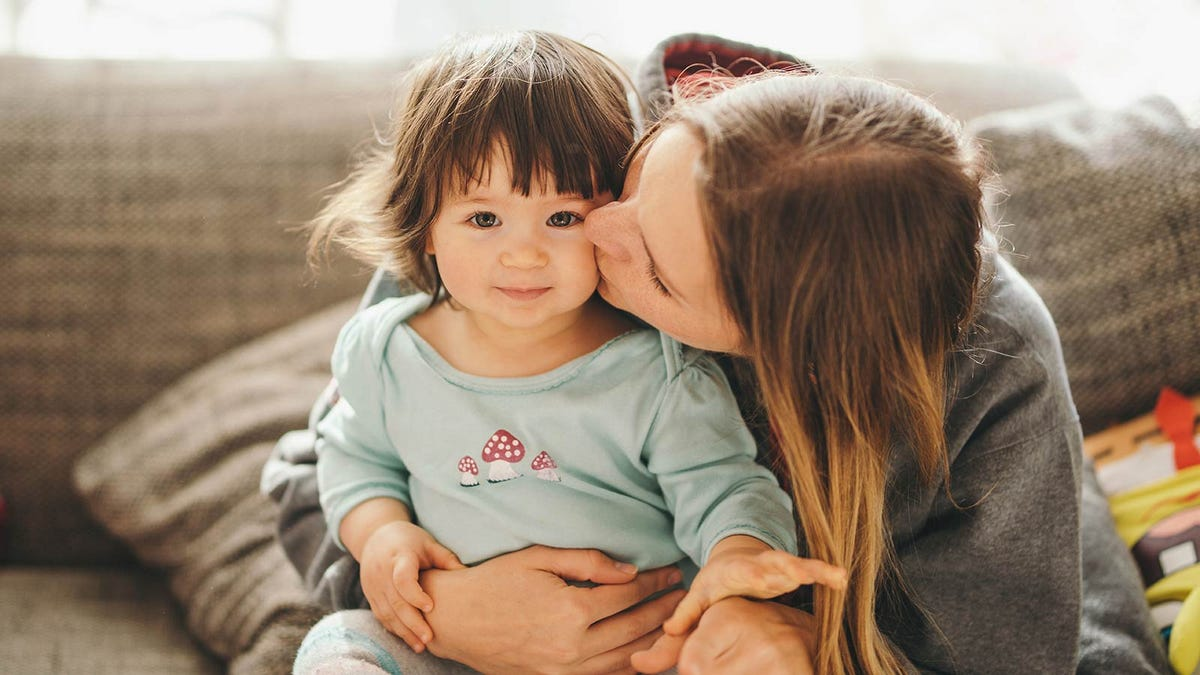 A woman kissing the cheek of a toddler sitting on her lap.
