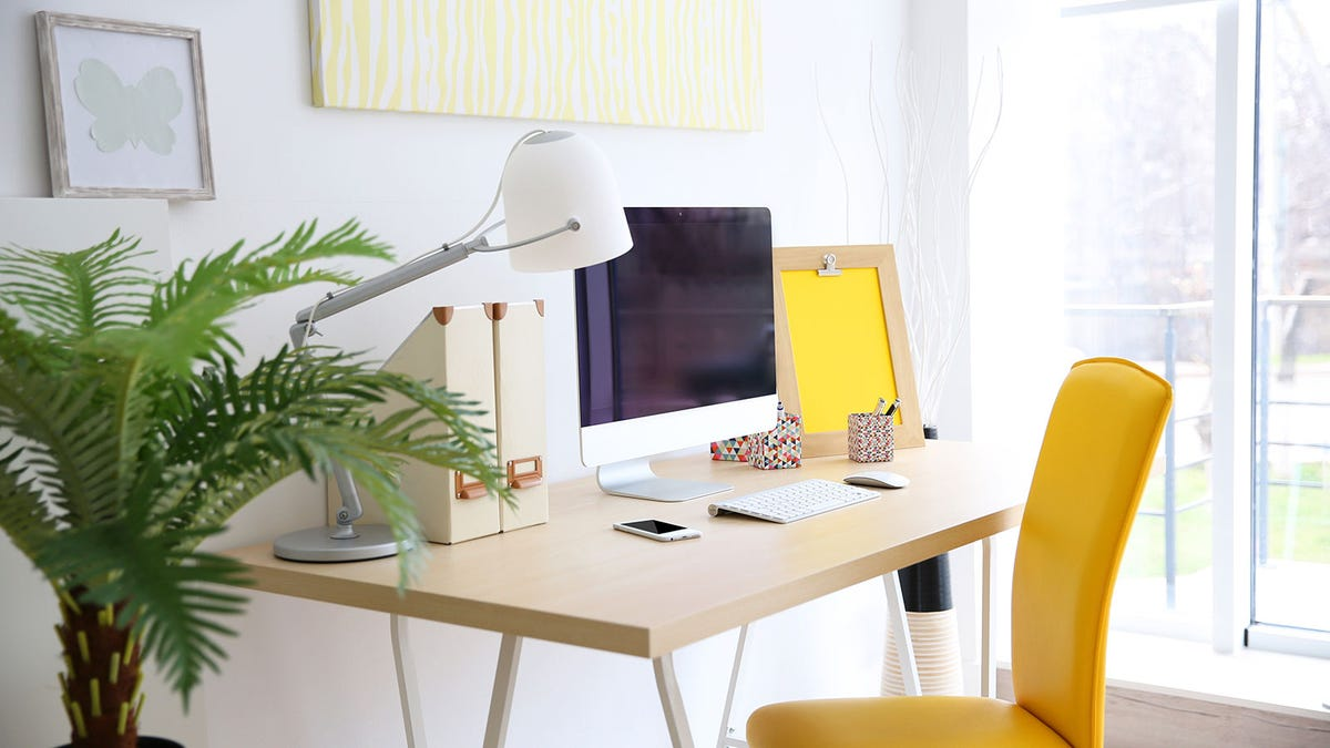 A sunny home office with a colorful yellow chair.