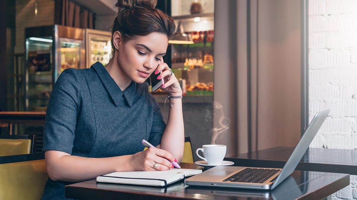 A young woman making a phone call in a coffee shop while taking notes.