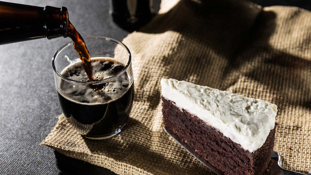A dark beer being poured from a bottle into a glass next to a piece of chocolate cake with white icing.