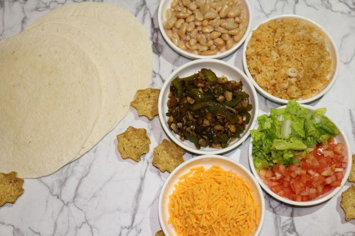 Multiple ingredients laid out including, tortillas, rice, beans, sauteed veggies, cheese, lettuce and tomatoes (with scattered tortilla chips)