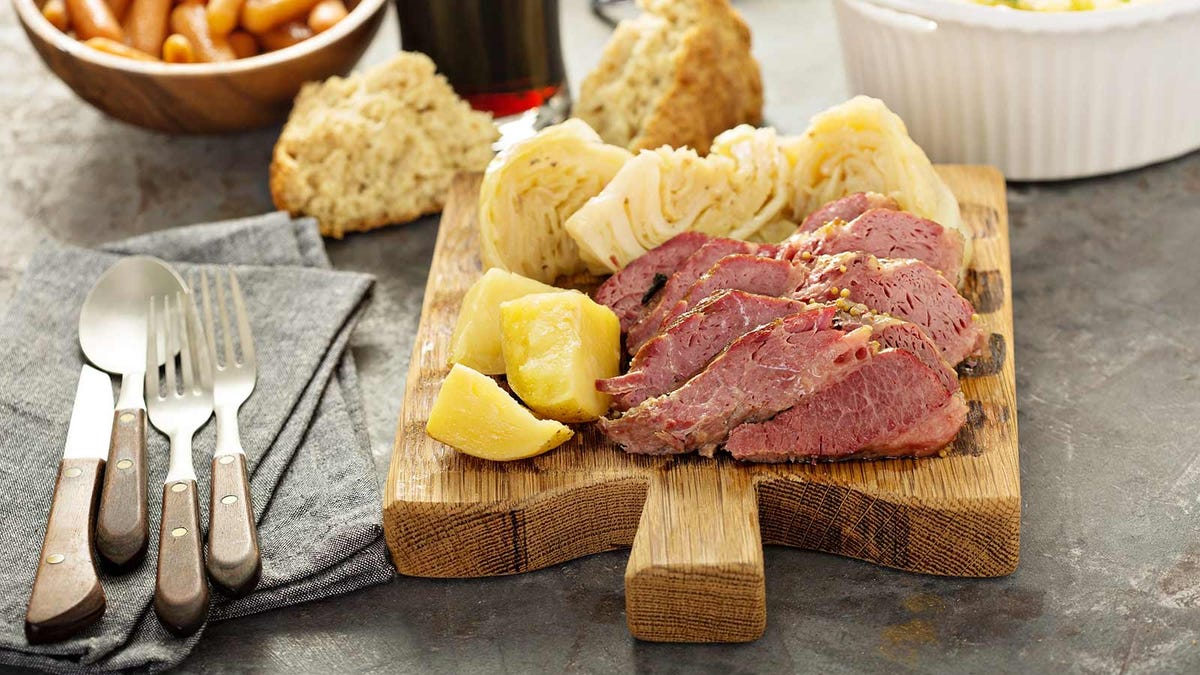 A cutting board platter with corned beef and cabbage on it.