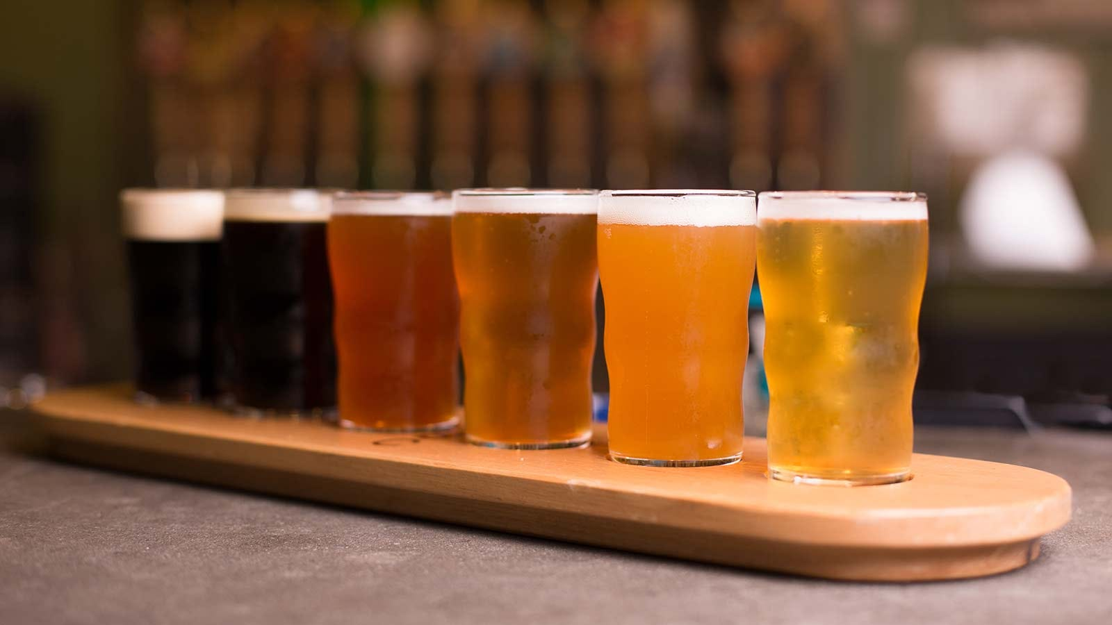 A flight of beers arranged in pint glasses on a plank.