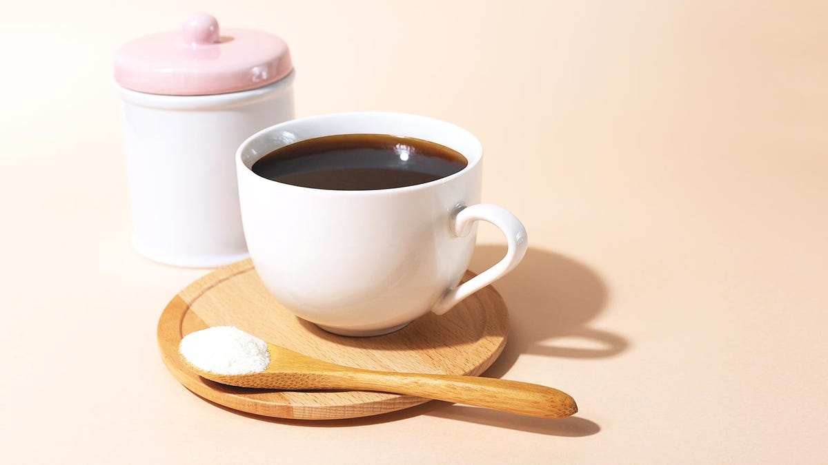 A cup of coffee on a bamboo platter beside a spoon loaded with collagen powder.