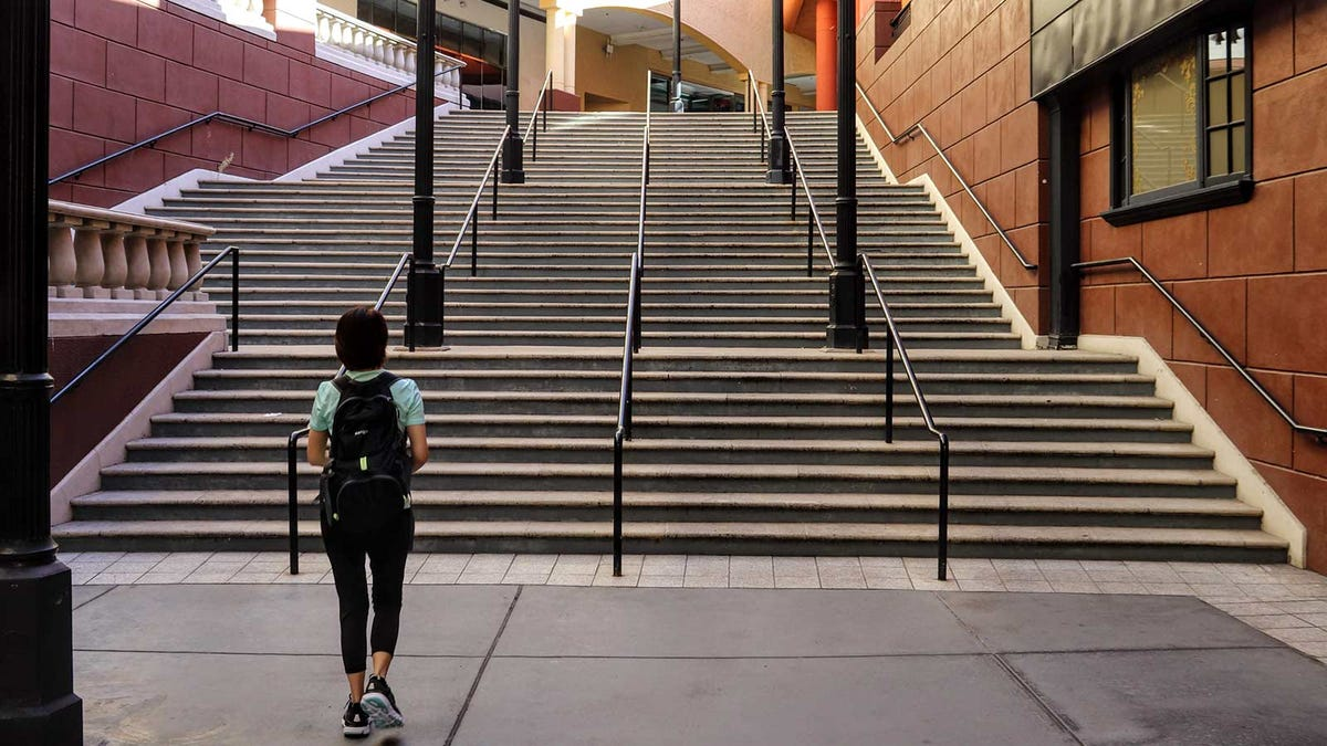 Person walking up the stairs of an otherwise completely vacant outdoor mall.