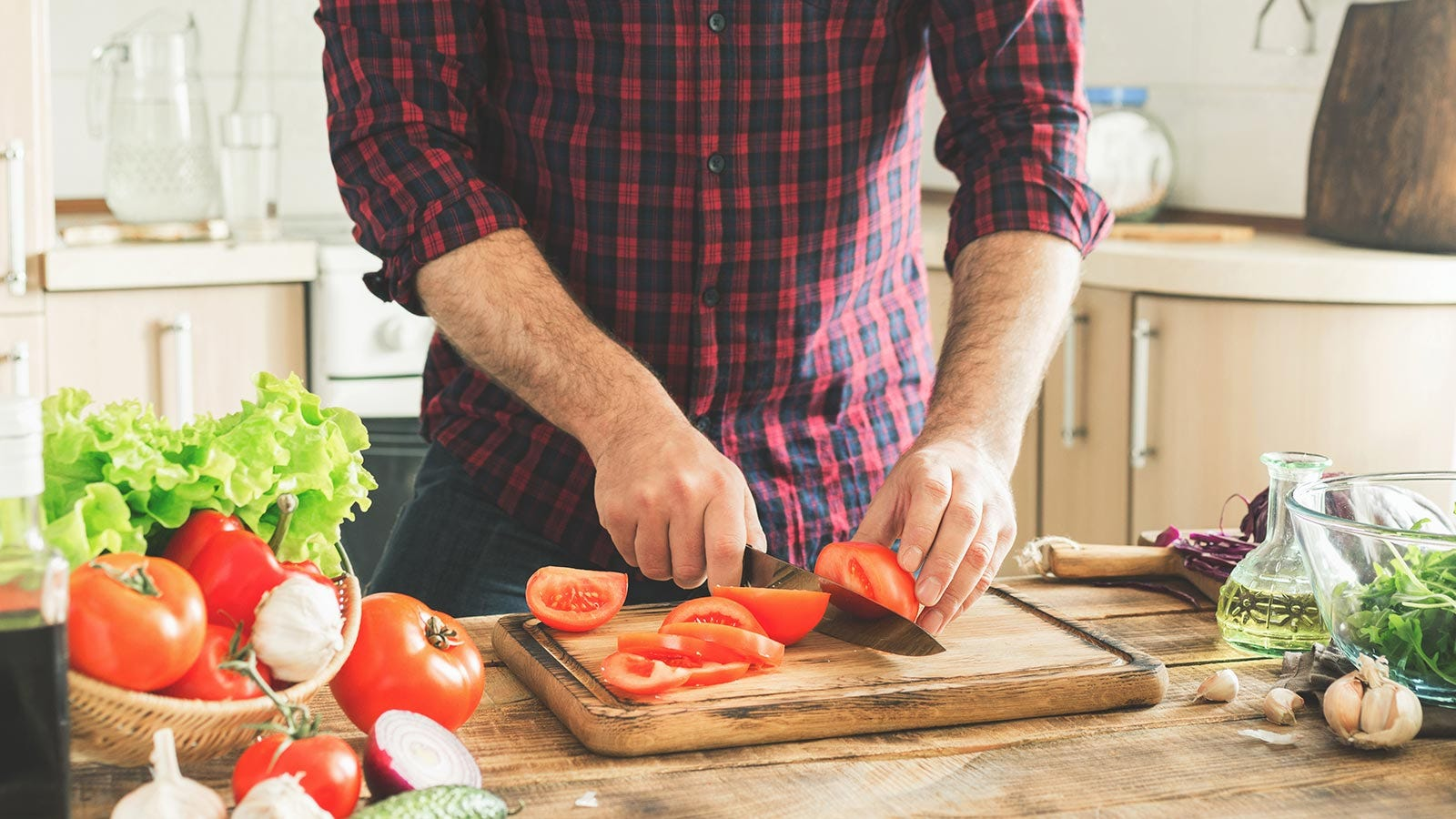 A man chopping fresh vegetables in a sunny kitchen.