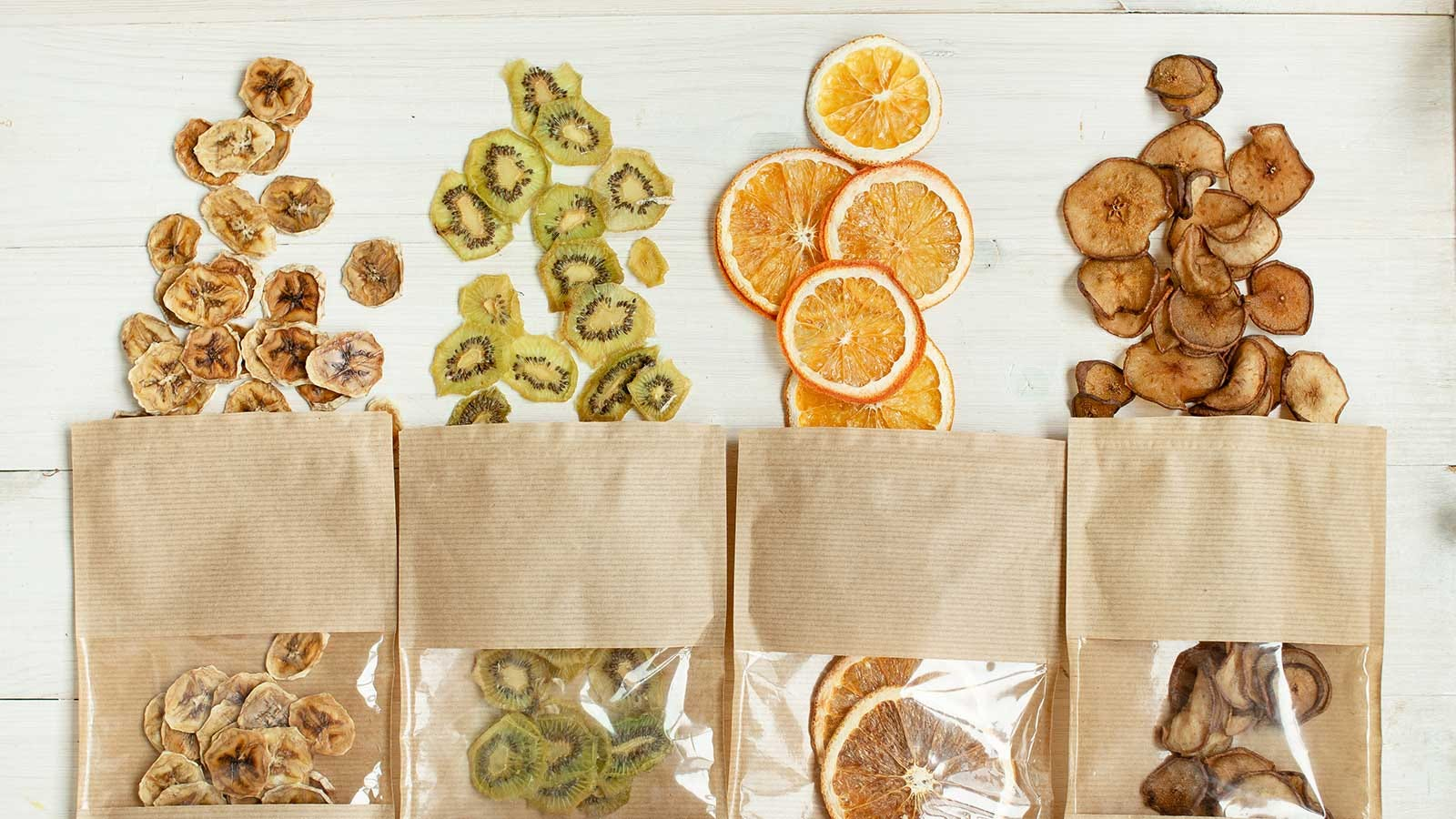Four paper bags of dehydrated fruit with some of the contents of each spilled out on a table.