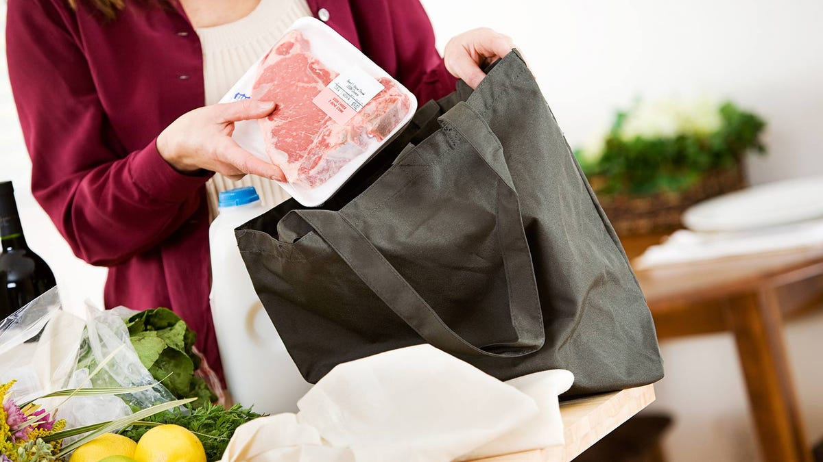 A woman's hand unpacking a package of meat from a a reusable grocery bag.