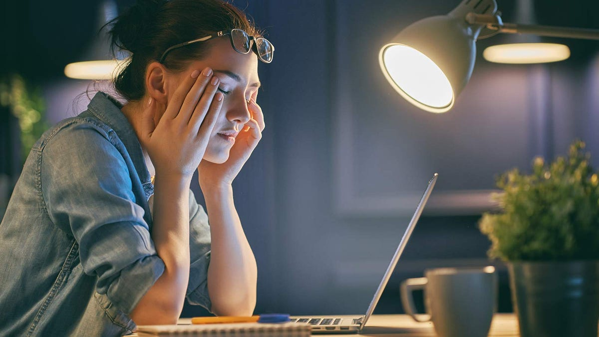 A woman sitting at a desk with a laptop open, resting her face on her hands with her eyes closed.