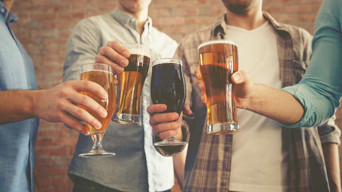 A group of guys toasting their pint glasses of beer.