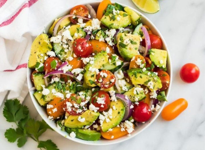A bowl of cucumber, tomato and avocado salad, topped with crumbled cheese and fresh herbs