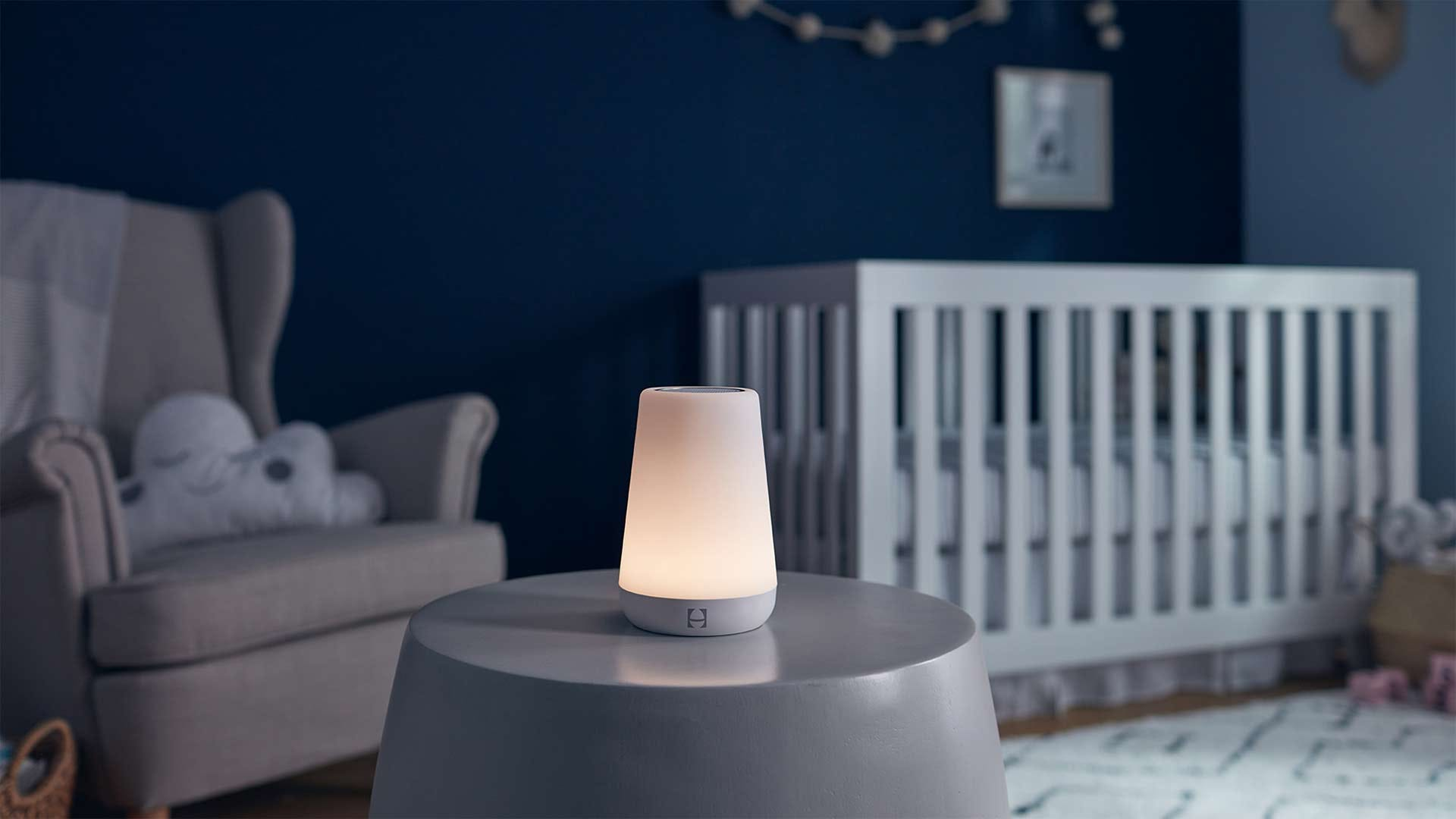 A Hatch Rest light in a peaceful blue and white baby nursery.