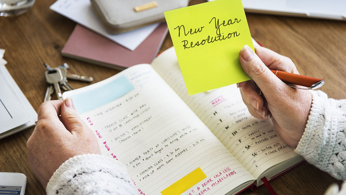 A woman putting a sticky note reminder in her calendar with a New Year's Resolution on it.