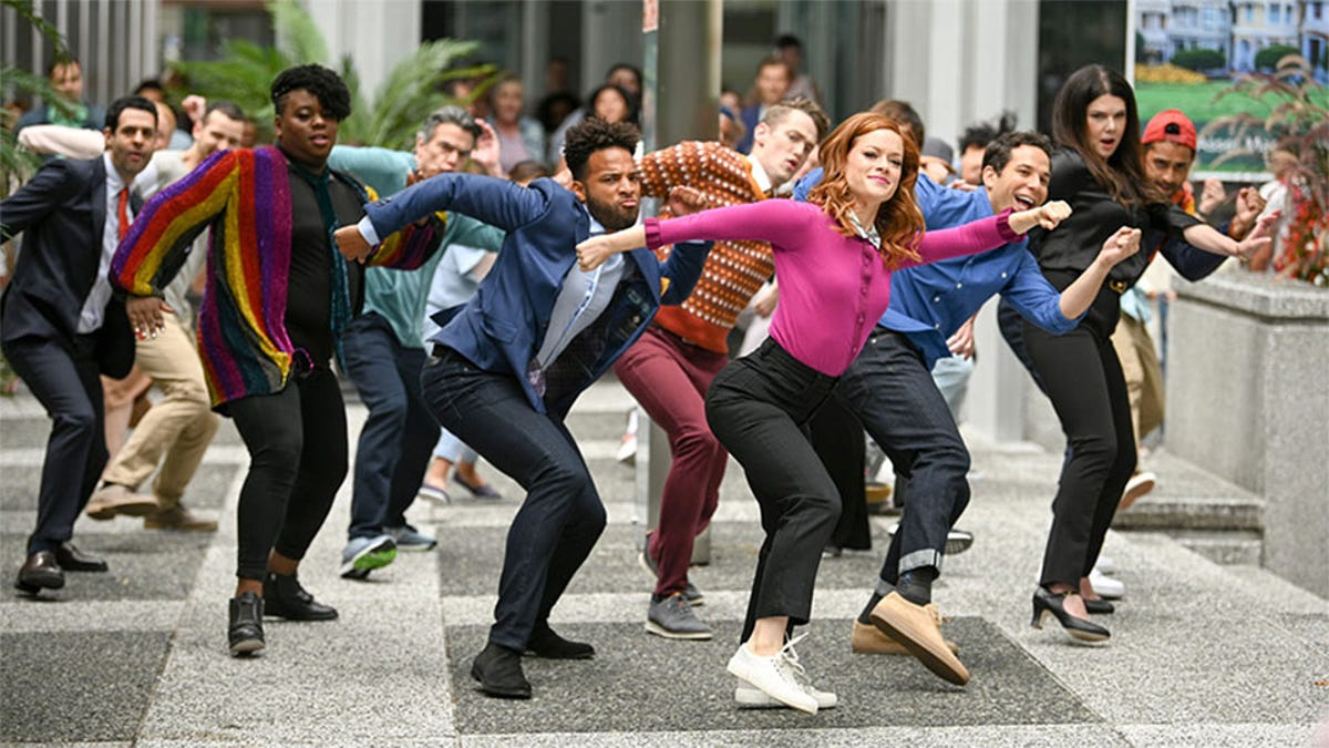 The cast of Zoey's Extraordinary Playlist dancing and singing in a public plaza.
