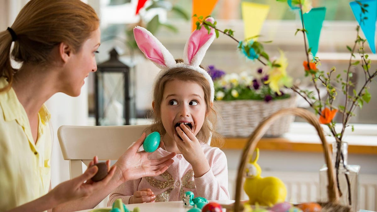 A woman holding a decorated egg out to a little girl, who's wearing bunny ears and eating a chocolate egg.