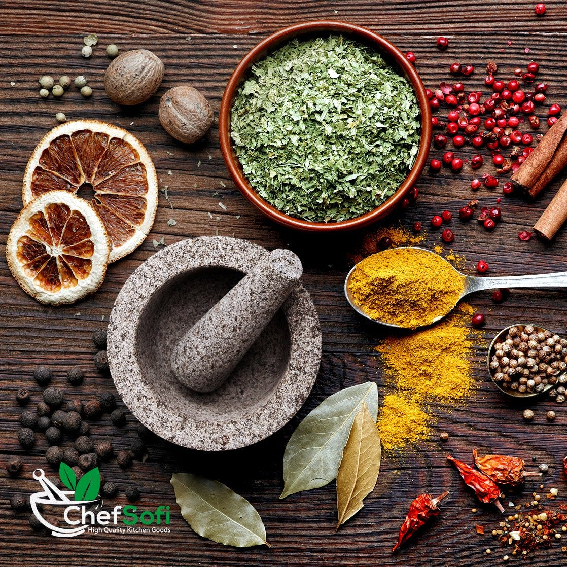 Mortar and pestle on a table surrounded by spices.