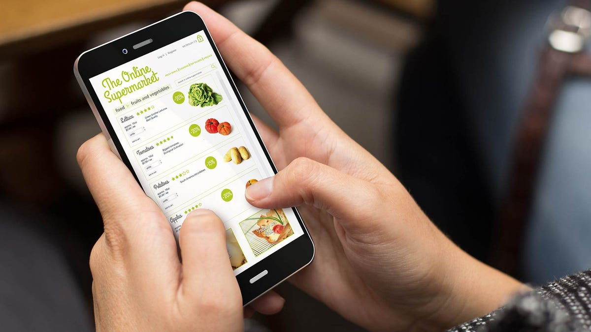 """Hands holding a smartphone with an """"Online Supermarket"""" app open."""