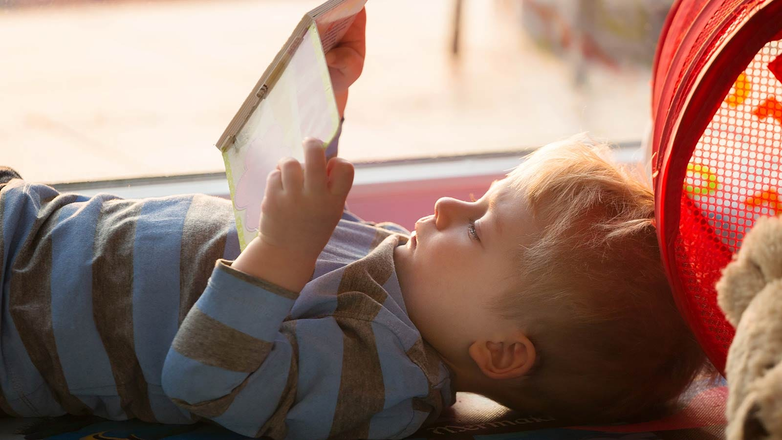 A little boy lying on the floor and looking at a book.