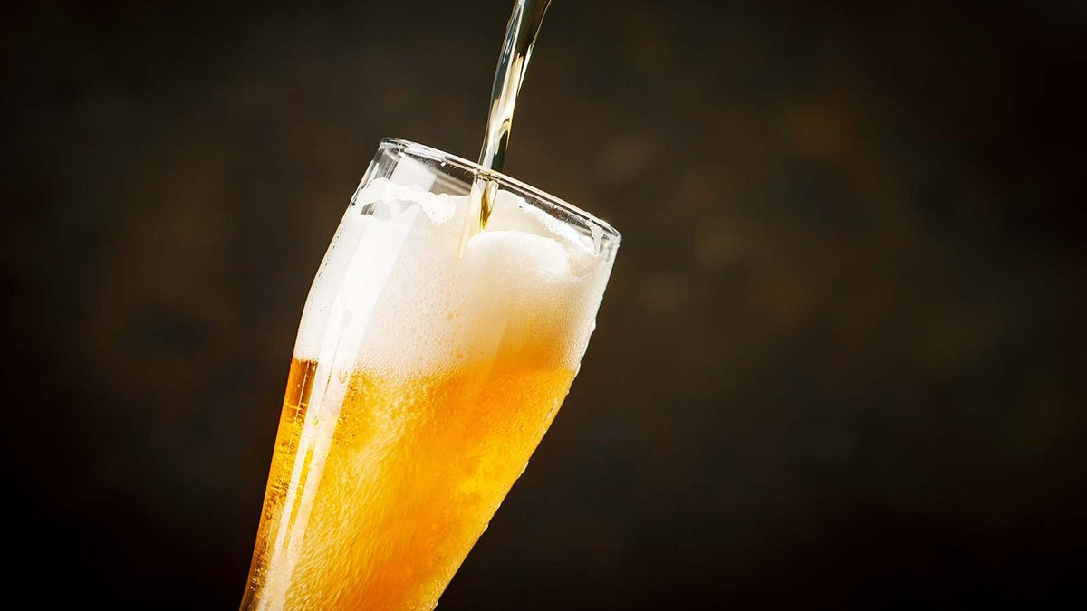 A stream of beer being poured into a large pilsner glass.
