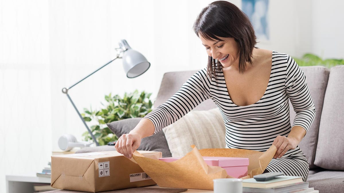 A woman opening a subscription box package in her living room.