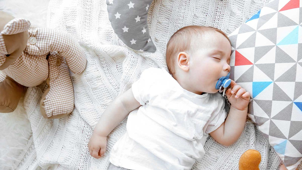 A baby asleep with a pacifier in its mouth.