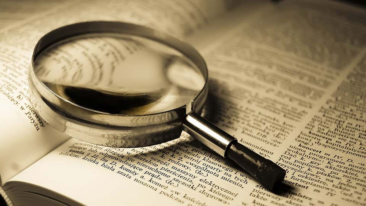 Magnifying glass resting on a dictionary. Will anyone notice it's not English-language? A clue for our alt-text readers.