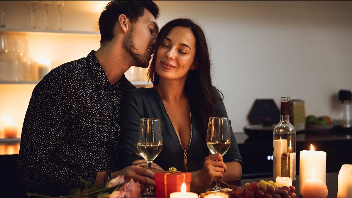A man and woman holding wine glasses at a table filled with candles.