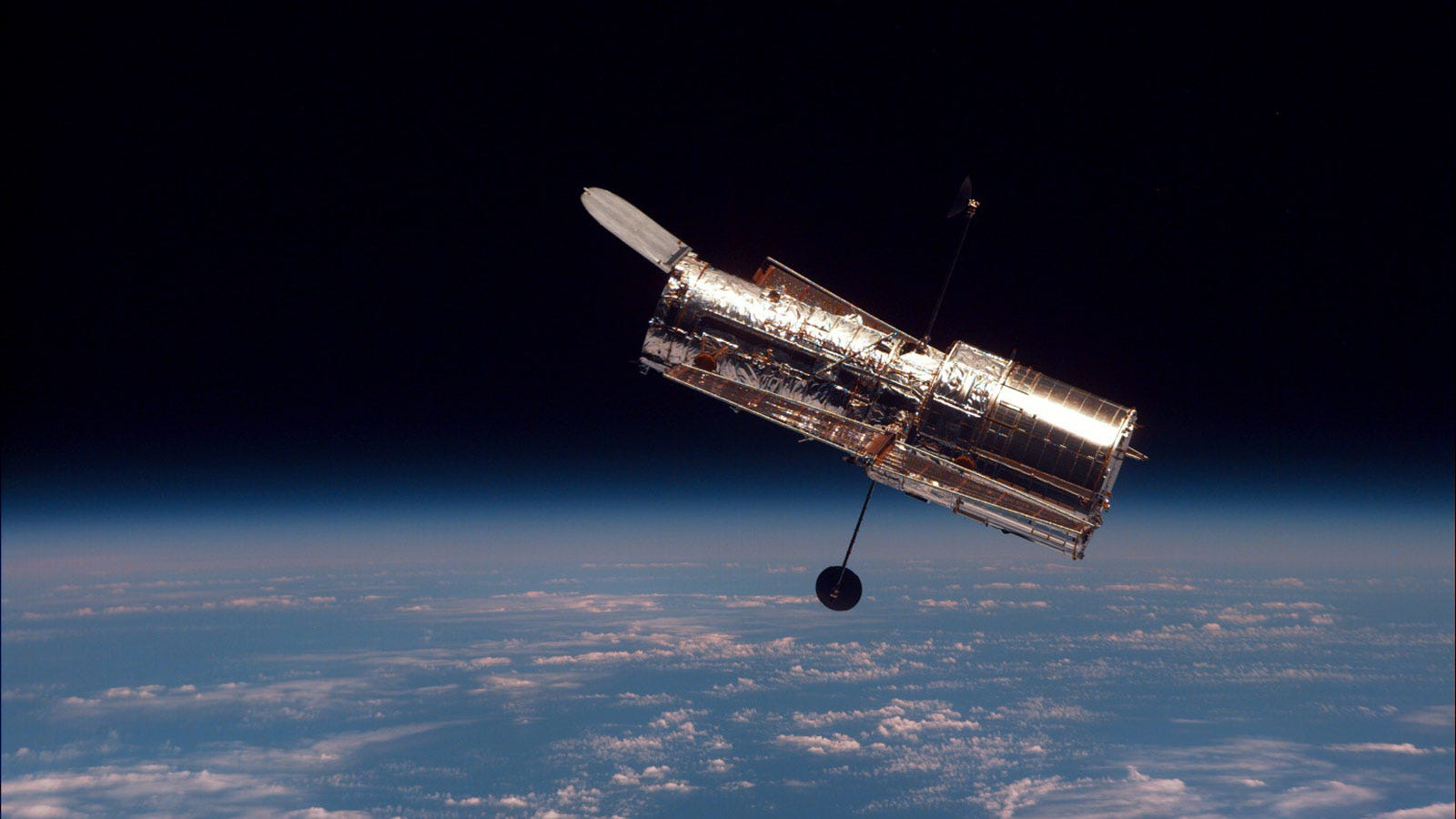 A photograph showing the Hubble Space Telescope floating in Earth orbit.