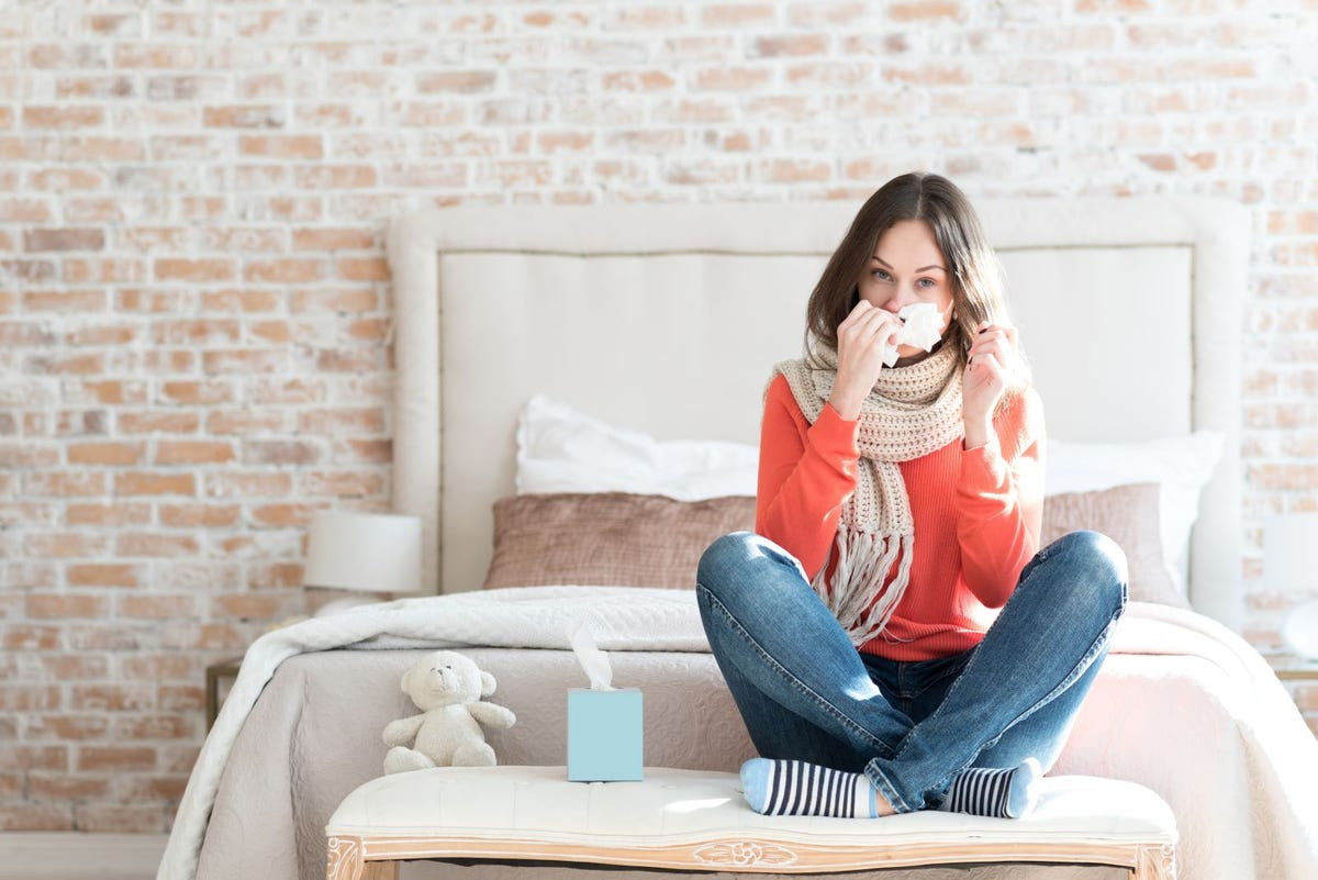 A woman with a cold sitting on a bench in a bedroom using a tissue to blow her nose.