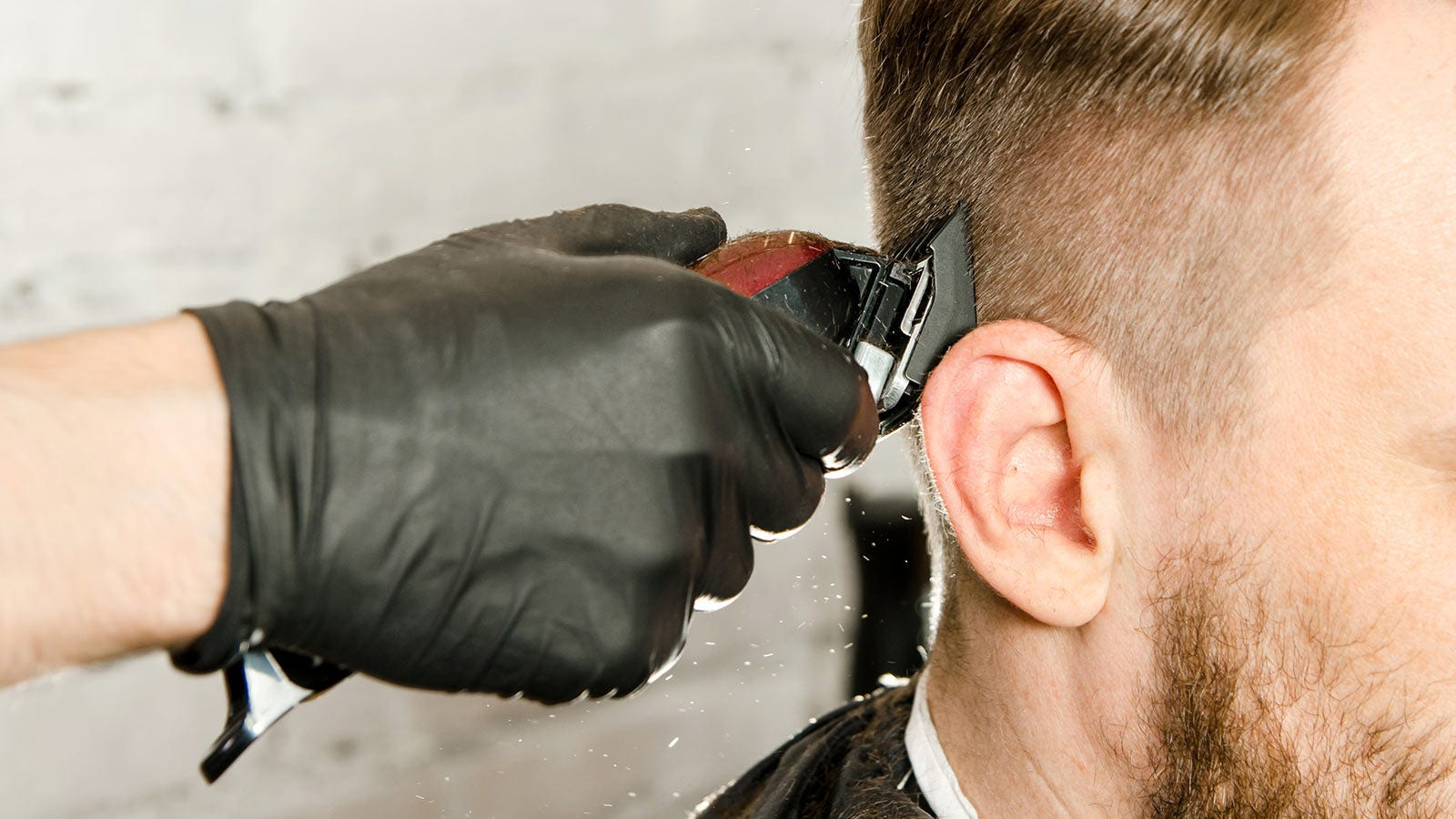 Man getting his hair faded by a barber using clippers.