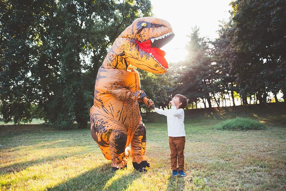 Boy looking up at someone dressed in an inflatable T. rex dinosaur suit.