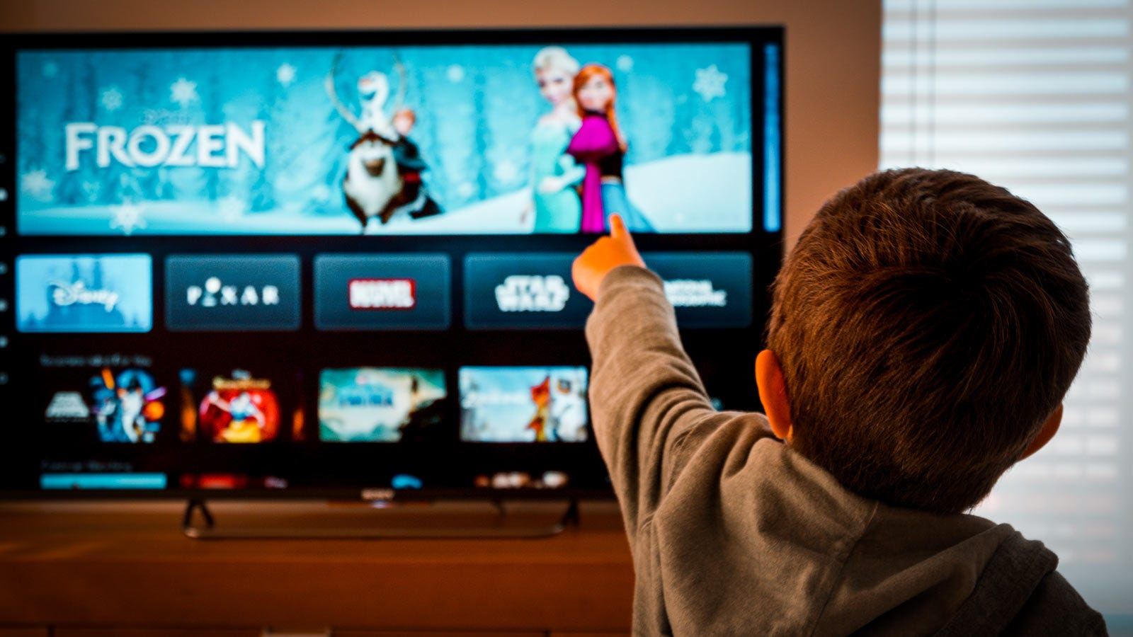 A boy watching TV, pointing excitedly at the Disney movie offerings.