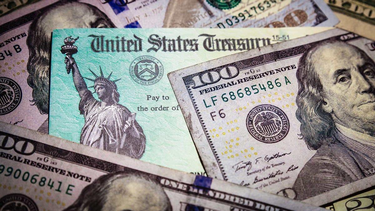 A treasuring check nestled among one hundred dollar bills.