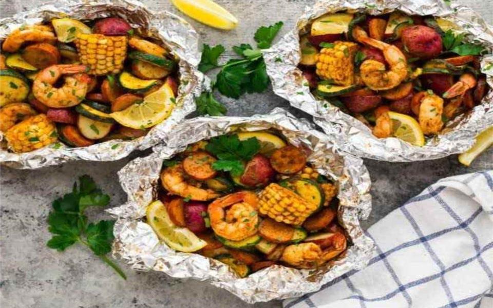 three foil dinners each holding, shrimp, corn, chicken sausage, potatoes zucchini and lemon.