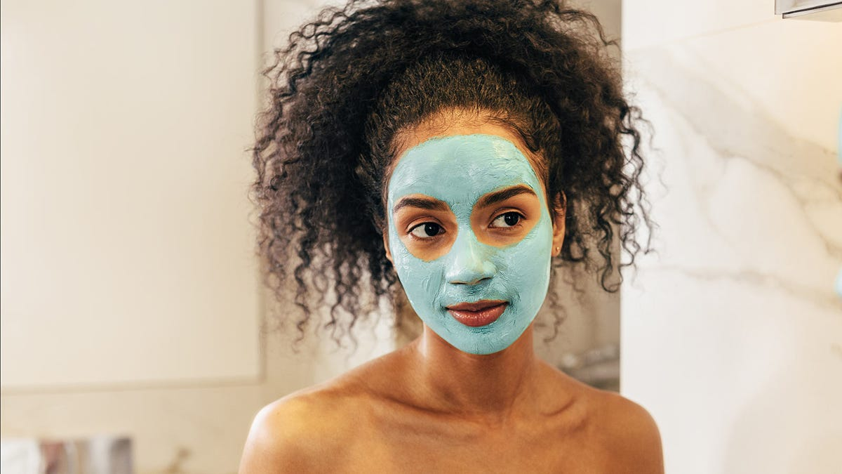 A woman with a green face mask applied.