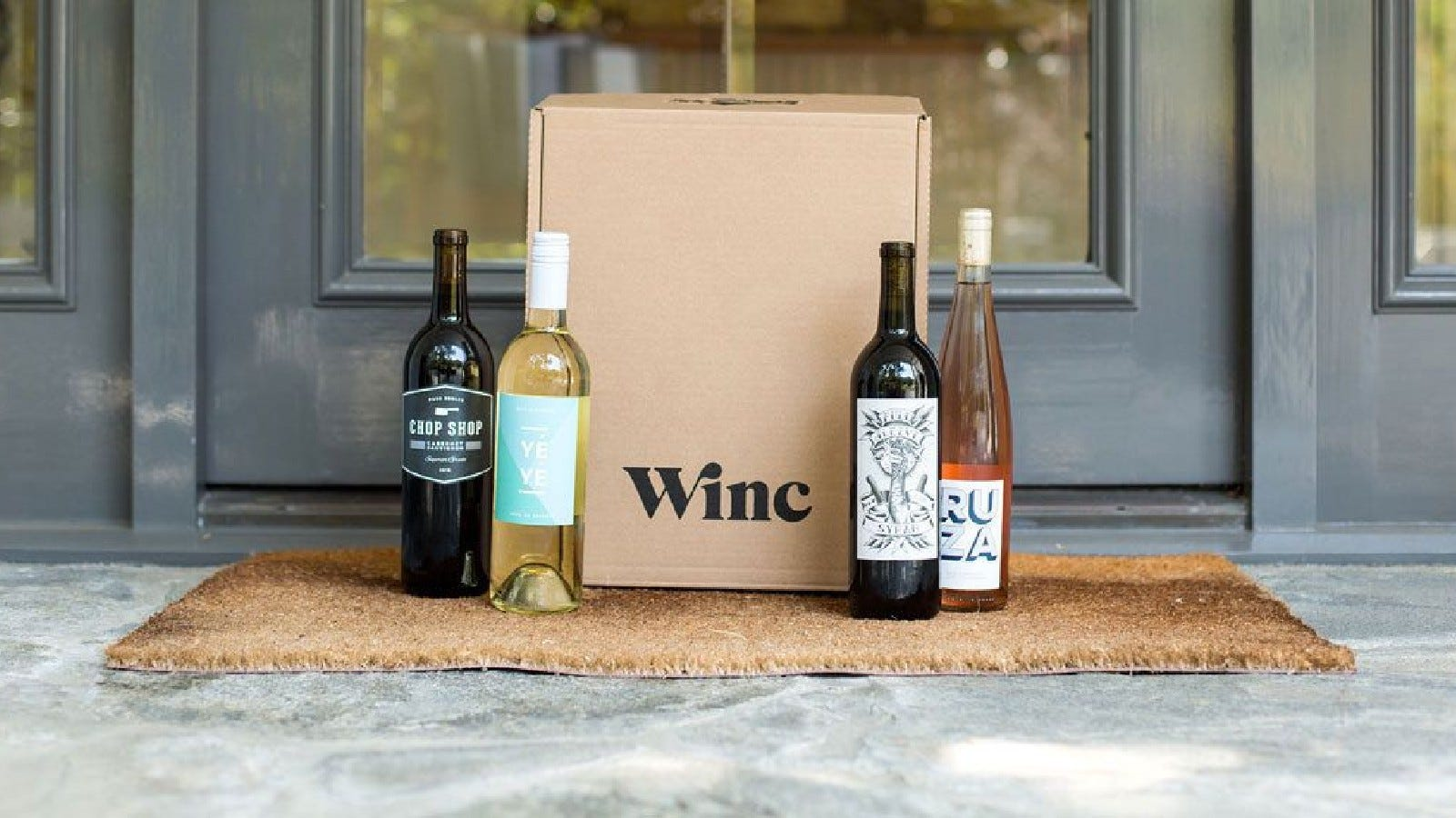 Four bottles of wine next to a Winc box sitting on a porch.