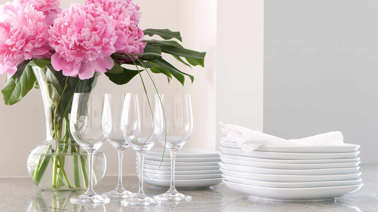 A stack of white plates, crystal ware, linens, and a vase filled with peonies, ready to be set out for dinner.