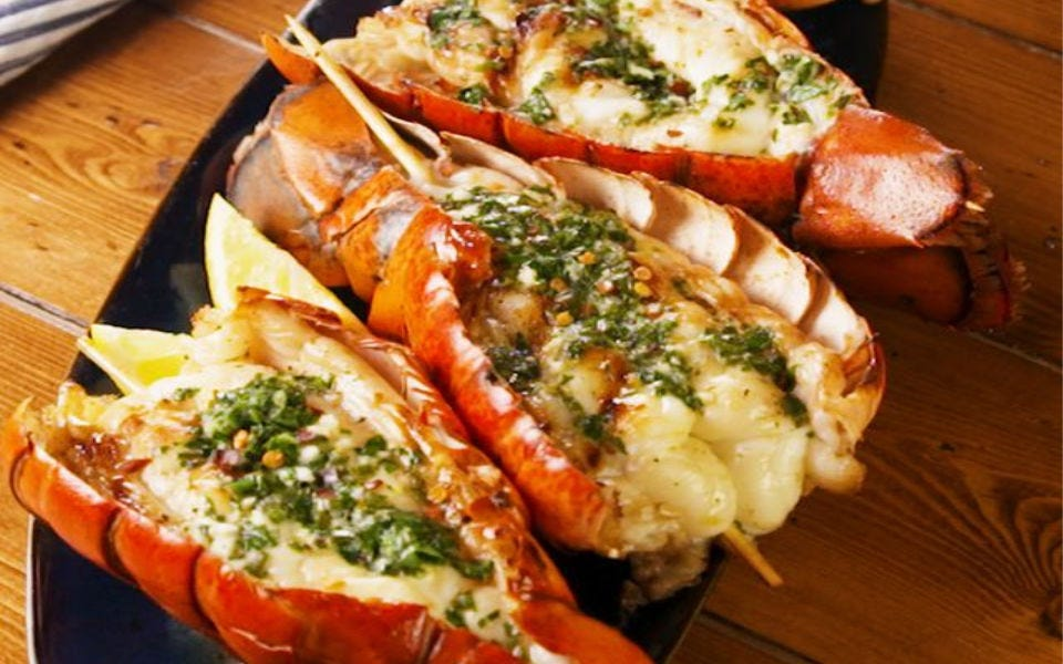 Three lobster tails, grilled to perfection and topped with a butter herb drizzle.