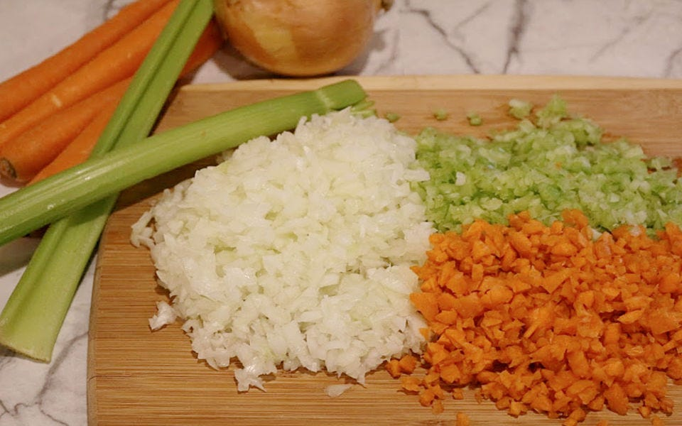 Mirepoix (carrots, onion, and celery) diced very small on a cutting board.