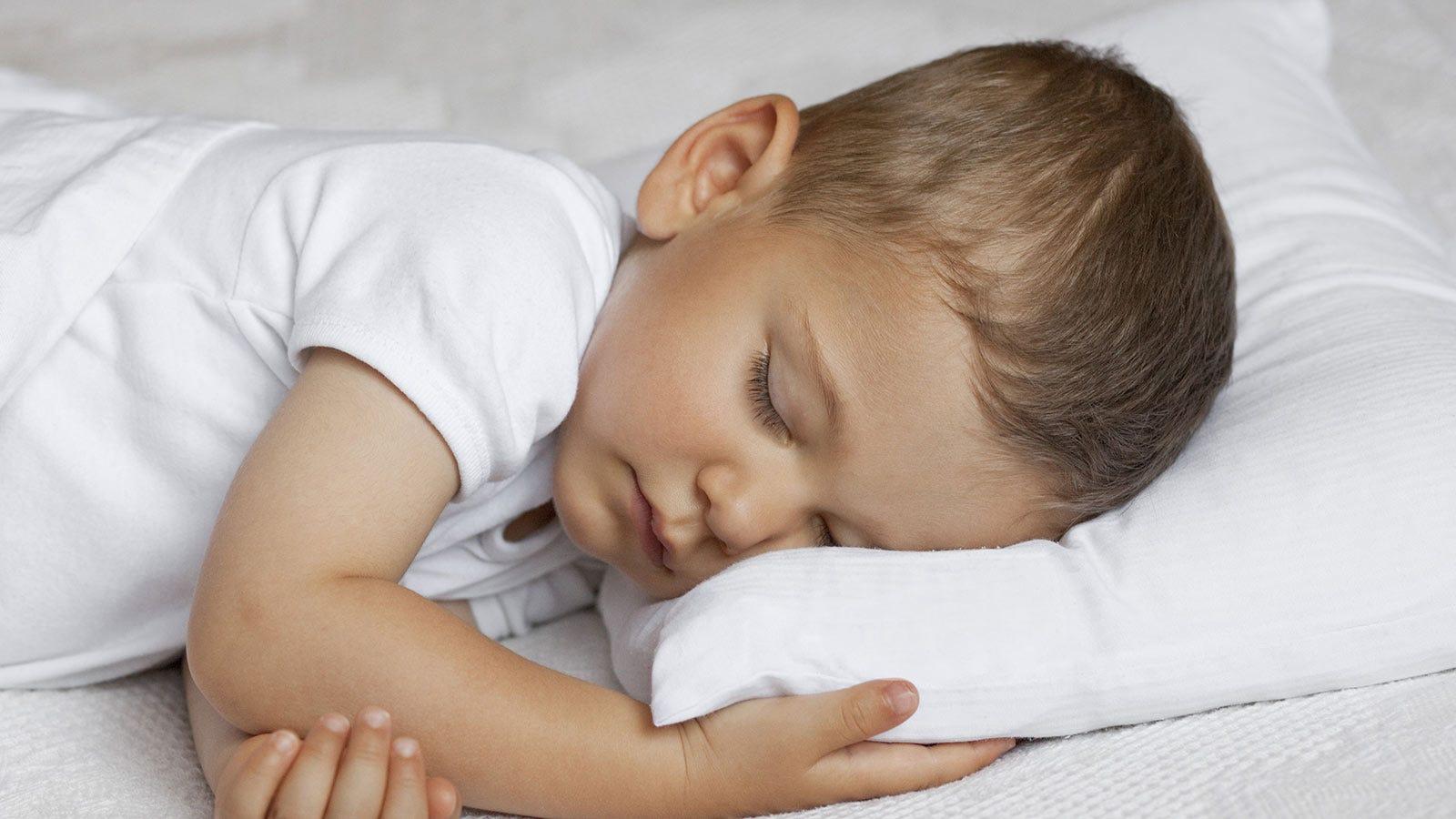 A toddler asleep on a pillow.